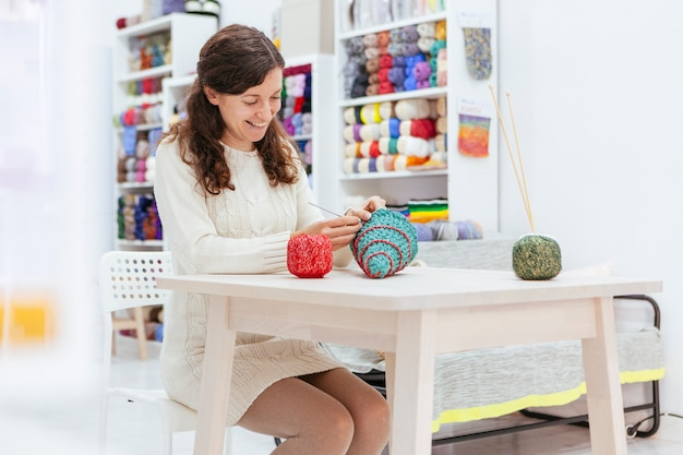 Femme joyeuse tricotant un arbre de noël avec des fils de laine