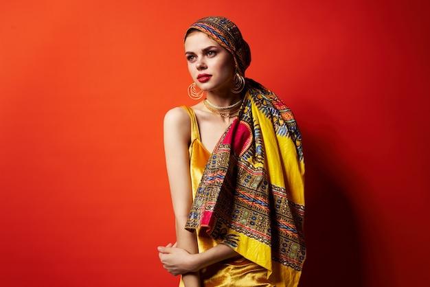 Femme joyeuse en turban multicolore look attrayant bijoux fond rouge