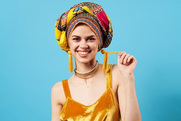 Femme joyeuse en turban multicolore look attrayant bijoux sourire fond isolé