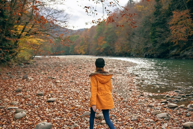 Femme joyeuse en vêtements d'automne près de la rivière forestière