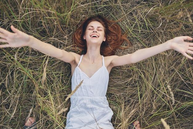 Une femme joyeuse vêtue d'une robe se trouve sur l'herbe reste la nature