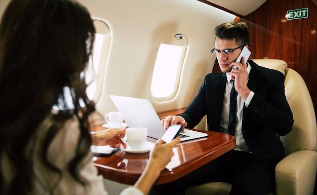 Femme joyeuse, vêtue d'une tenue de soirée et de lunettes, qui tape quelque chose sur son ordinateur portable et parle au téléphone, volant en classe affaires avec son collègue.