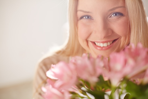 Femme joyful avec des fleurs roses