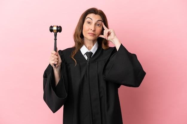 Femme juge d'âge moyen isolée sur fond rose en pensant à une idée