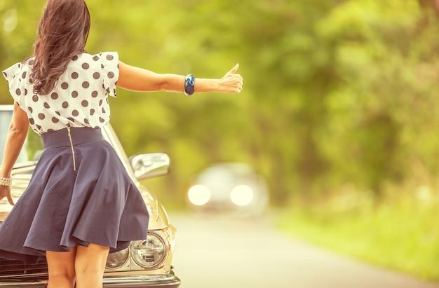 Femme en jupe courte faisant de l'auto-stop près de la voiture debout à côté de son véhicule d'époque en panne.