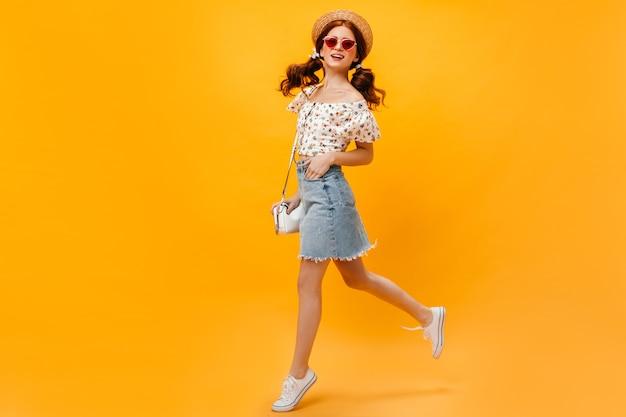 Femme en jupe en jean, t-shirt blanc et canotier sautant sur fond orange. femme à lunettes de soleil souriant.