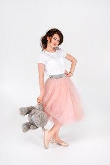 Femme en jupe rose tenant un gros ours en peluche doux