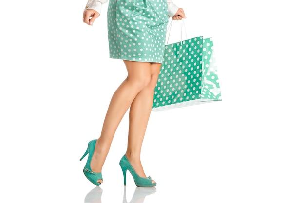 Femme en jupe verte avec sac à provisions isolé sur fond blanc