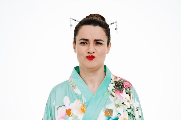 Femme en kimono japonais traditionnel étant ennuyé de souffler des joues sur blanc