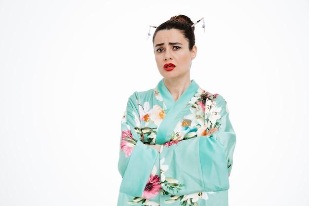 Femme en kimono japonais traditionnel avec une expression sceptique avec les bras croisés sur blanc