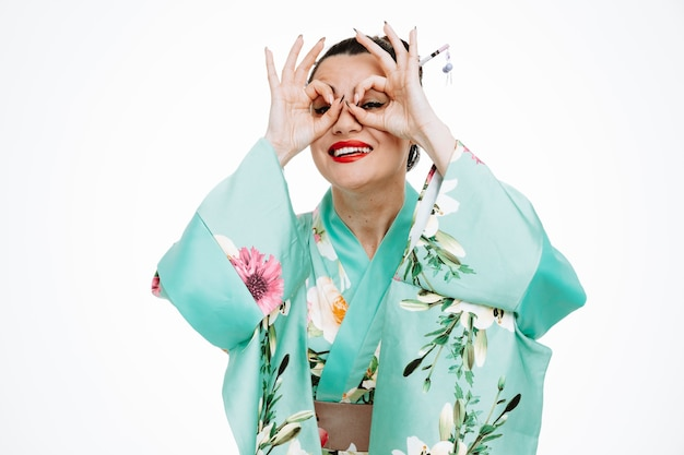 Femme en kimono japonais traditionnel faisant un geste binoculaire à travers les doigts heureux et joyeux souriant largement sur blanc