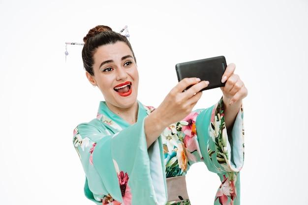 Femme en kimono japonais traditionnel heureux et positif faisant selfie à l'aide d'un smartphone souriant joyeusement sur blanc