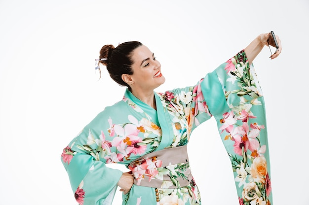 Femme en kimono japonais traditionnel souriant heureux et positif faisant gaiement selfie à l'aide de smartphone sur blanc
