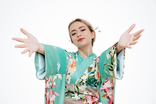 Femme en kimono japonais traditionnel souriant joyeusement faisant un geste de bienvenue large ouvrant les mains sur blanc