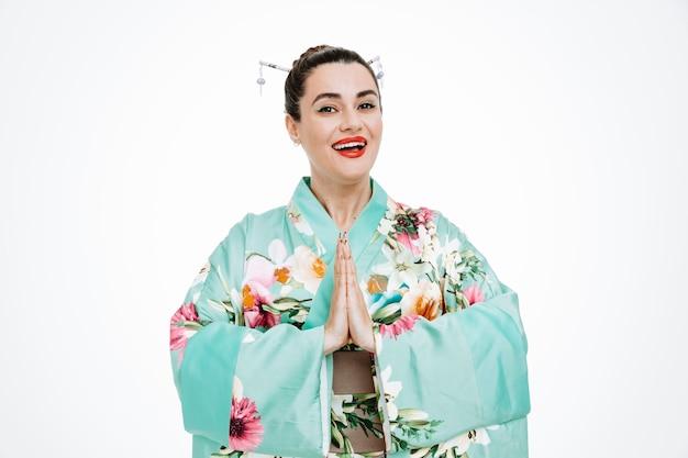 Femme en kimono japonais traditionnel souriant main dans la main en geste de salutation sur blanc