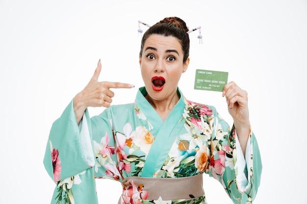 Femme en kimono japonais traditionnel tenant une carte de crédit pointant avec l'index dessus avec le sourire sur un visage heureux sur blanc