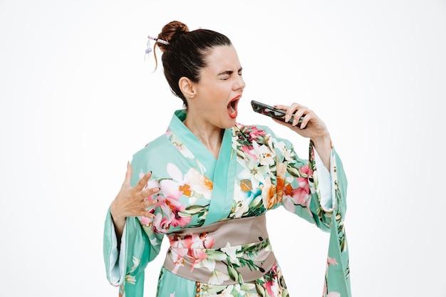 Femme en kimono japonais traditionnel tenant un smartphone criant d'être excité sur blanc