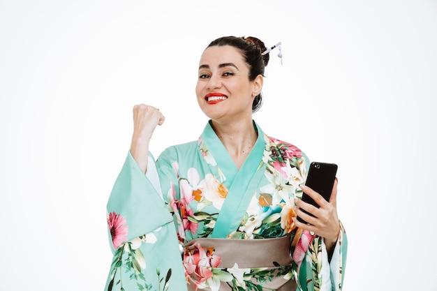 Femme en kimono japonais traditionnel tenant un smartphone heureux et excité, serrant le poing sur blanc