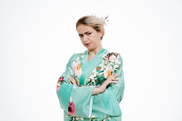 Femme en kimono japonais traditionnel avec un visage en colère fronçant les sourcils avec les bras croisés sur blanc