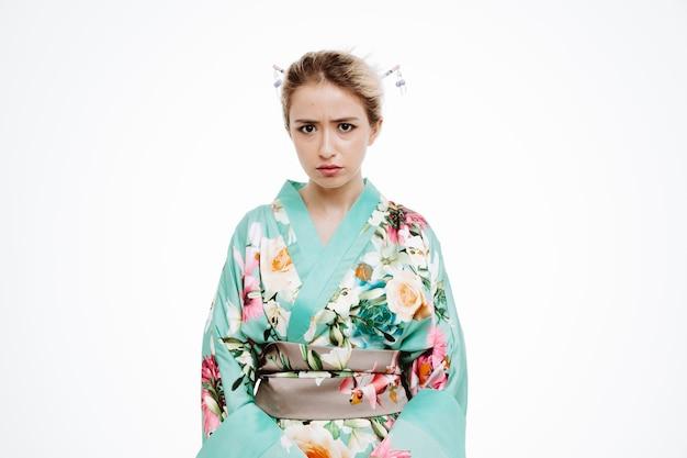 Femme en kimono japonais traditionnel avec un visage fronçant les sourcils en colère sur blanc