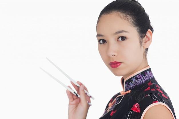 Femme en kimono tenant des baguettes