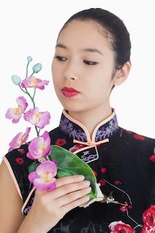 Femme en kimono tenant l'orchidée