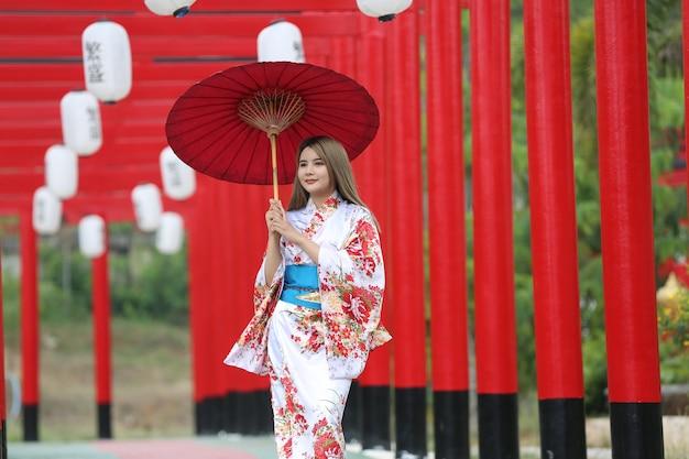 Une femme en kimono tenant un parapluie entrant dans le sanctuaire, dans le jardin japonais.