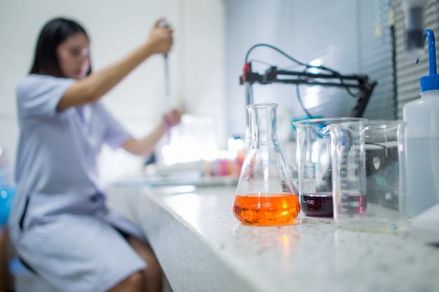 Femme en laboratoire avec des contenants de produits chimiques