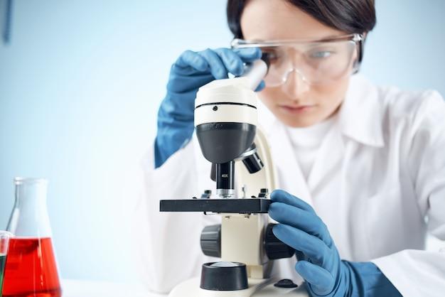 Femme en laboratoire regardant à travers la science de la biotechnologie en gros plan au microscope