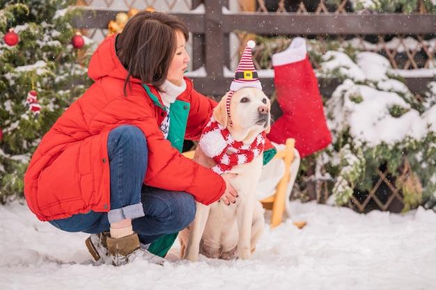 Une femme avec un labrador doré dans une écharpe est assise près d'un arbre de noël décoré et d'un traîneau lors d'une chute de neige en hiver dans la cour d'un immeuble résidentiel.