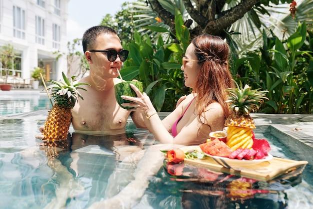 Femme laissant son petit ami essayer un cocktail de pastèque