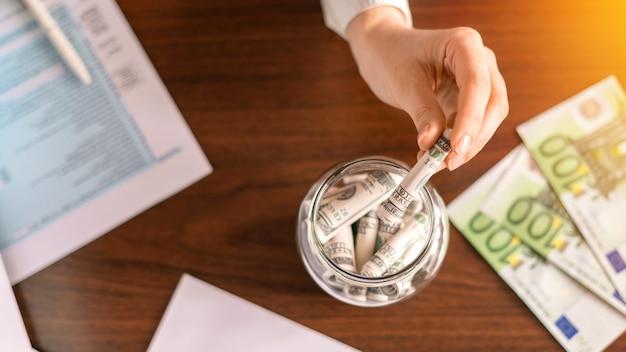 Femme laissant tomber un billets dans un bocal avec des billets roulés sur la table. des papiers, de l'argent sur la table