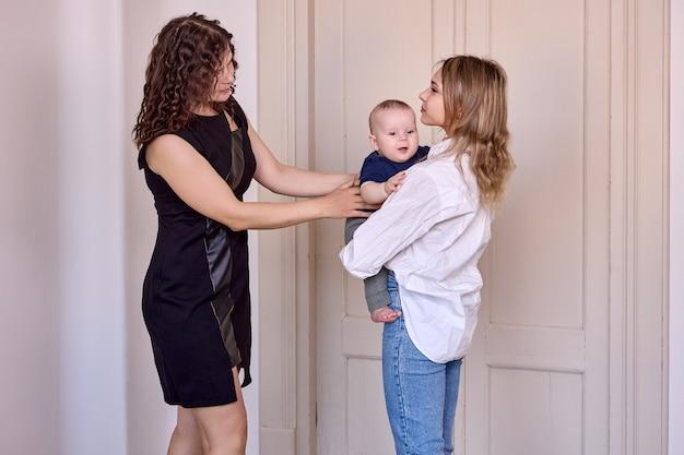Une femme laisse un bébé heureux avec une baby-sitter à l'intérieur