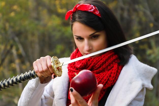 Une femme avec une lame tranchante dans ses mains est sur le point de couper une pomme rouge.