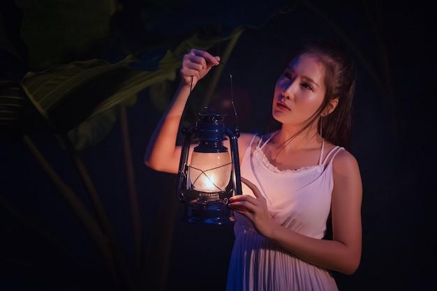 Femme avec lanterne vintage dehors la nuit