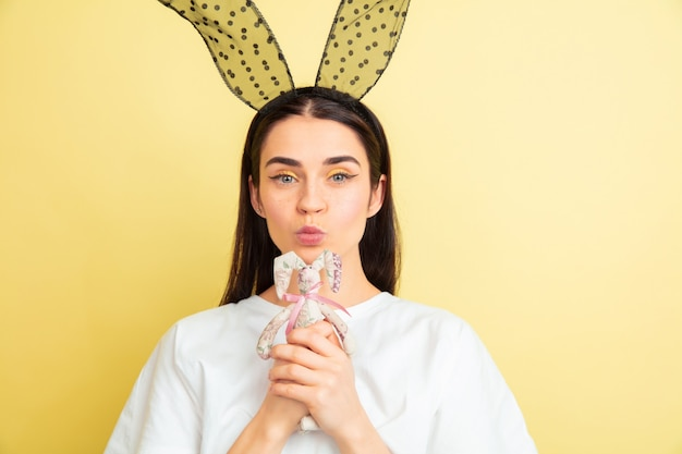 Femme de lapin de pâques avec des émotions vives sur le mur jaune du studio