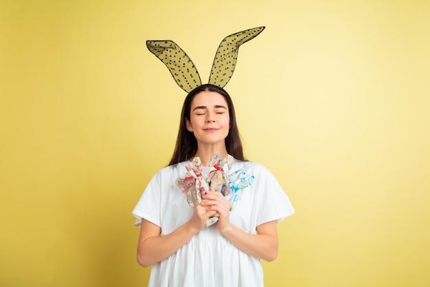 Femme de lapin de pâques avec des émotions vives sur mur jaune