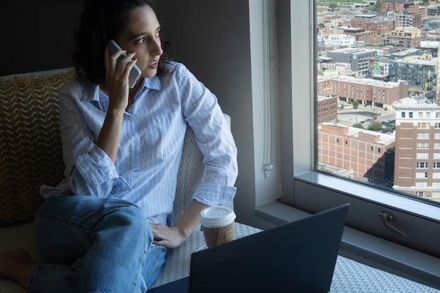 Femme latina parlant au téléphone avec un ordinateur portable et un café devant la fenêtre avec la ville, concept du mois latin du patrimoine, avec espace de copie