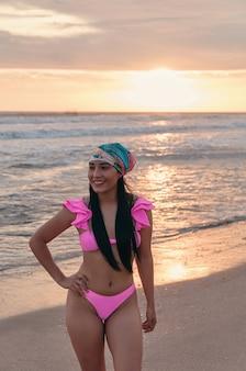 Une femme latina portant un maillot de bain d'été rose et un bandana au bord de la mer avec le coucher du soleil sur le dos