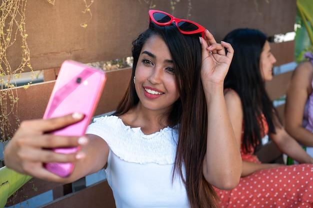 Femme latina prenant un selfie pour les médias sociaux jeune brune utilisant la technologie pour prendre une photo