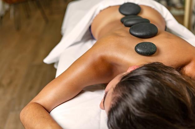 Femme latina relaxante avec thérapie aux pierres avec des pierres volcaniques chaudes sur le dos dans un spa de santé. concept de spa.