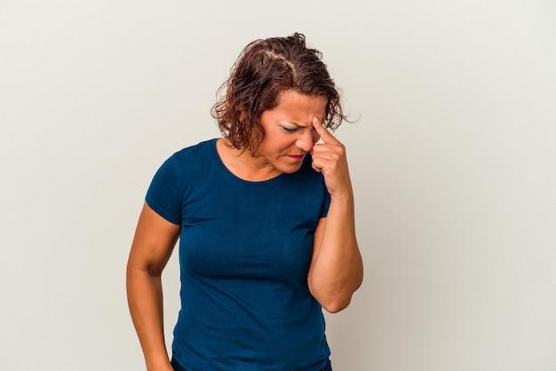 Femme latine d'âge moyen isolée sur fond blanc ayant un mal de tête, touchant le devant du visage.