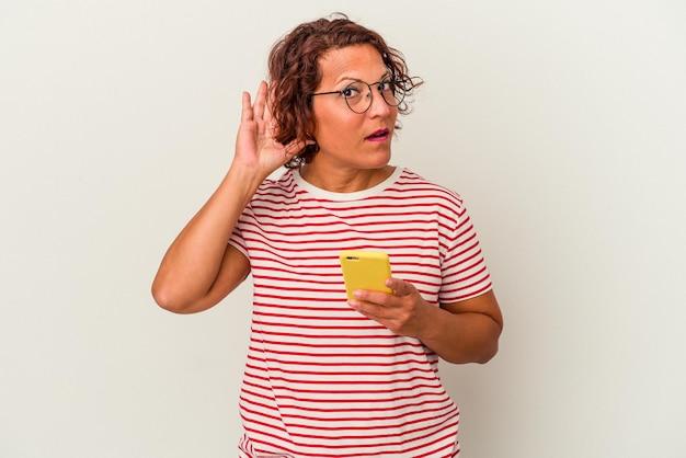 Femme latine d'âge moyen isolée sur fond blanc essayant d'écouter un potin.