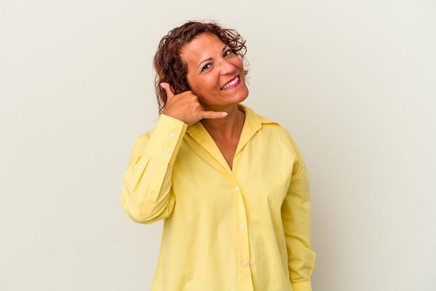 Femme latine d'âge moyen isolée sur fond blanc montrant un geste d'appel de téléphone portable avec les doigts.
