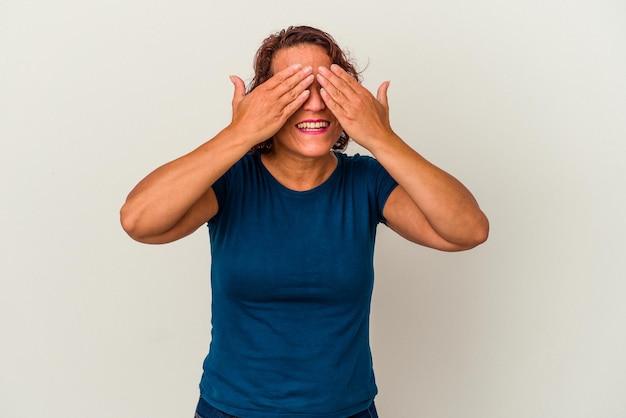 Femme latine d'âge moyen isolée sur fond blanc peur couvrant les yeux avec les mains.