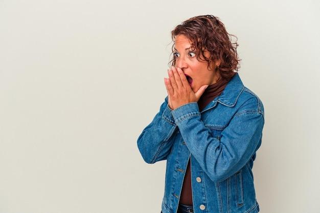 Femme latine d'âge moyen isolée sur fond blanc réfléchie à la recherche d'un espace de copie couvrant la bouche avec la main.