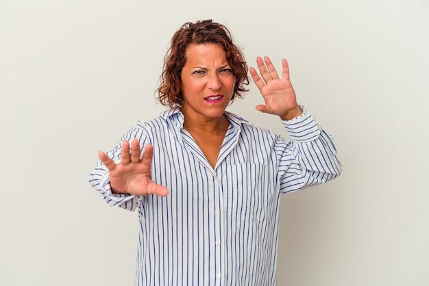 Femme latine d'âge moyen isolée sur fond blanc rejetant quelqu'un montrant un geste de dégoût.