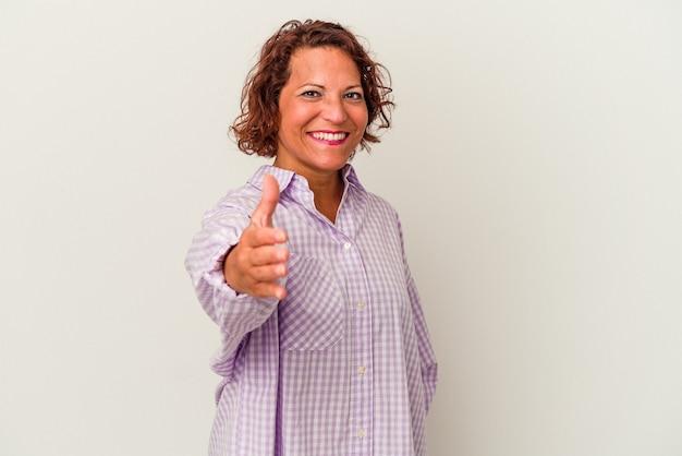 Femme latine d'âge moyen isolée sur fond blanc s'étendant la main à la caméra en geste de salutation.