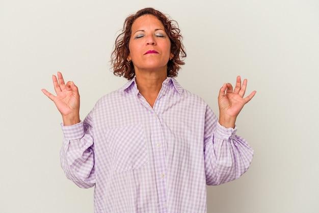 Une femme latine d'âge moyen isolée sur fond blanc se détend après une dure journée de travail, elle fait du yoga.