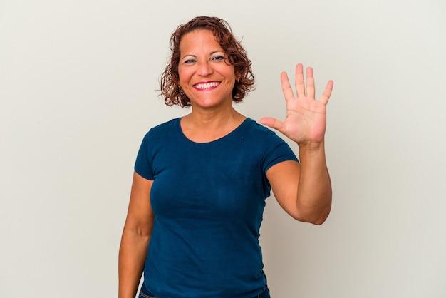 Femme latine d'âge moyen isolée sur fond blanc souriant joyeux montrant le numéro cinq avec les doigts.